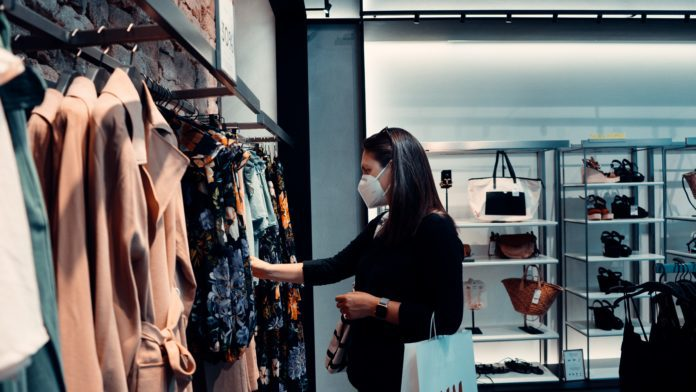 Customer experience changes during pandemic for consumers, like this woman shopping retail while wearing a mask.